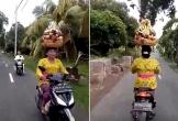 Nữ quái xế bình thản chạy xe máy với giỏ hoa quả... trên đầu