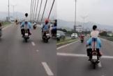 Bé gái đứng trên yên xe máy đang lao vun vút trên đường